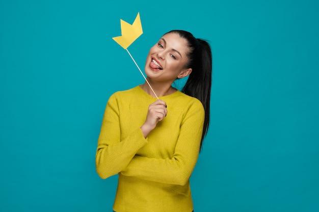 Moça engraçada que mantém a coroa de papel e mostrando a língua