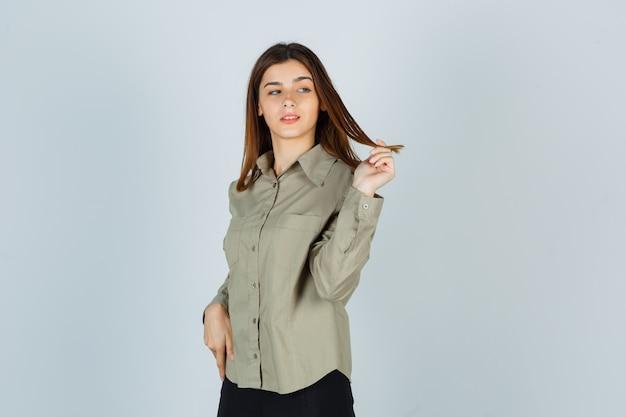 Moça enrolando o cabelo nos dedos enquanto desvia o olhar de camiseta, saia e parece pensativa. vista frontal.