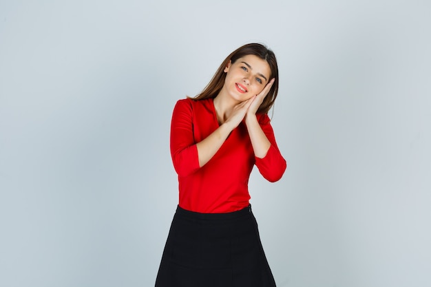 Moça fazendo travesseiro no rosto nas mãos com blusa vermelha, saia e parecendo com sono