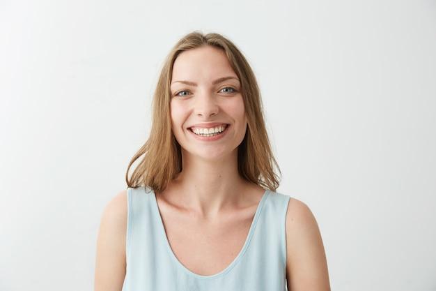 Moça feliz alegre sincera com olhos azuis, sorrindo, rindo.