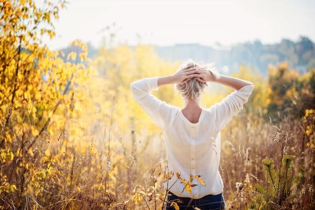 Moça feliz que aprecia a beleza do dia ensolarado do outono na grama alta em um parque do outono. vista de trás.
