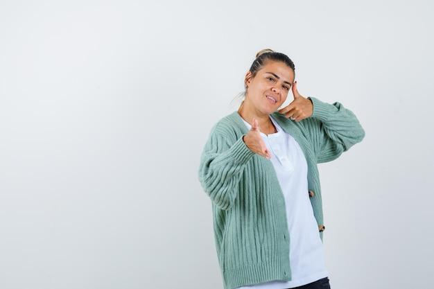 Moça fingindo mostrar algo em camiseta, jaqueta e linda