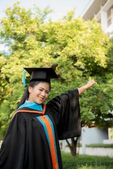 Moça graduada que veste um chapéu preto da borla.