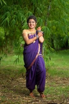 Moça indiana bonita no saree tradicional posando ao ar livre