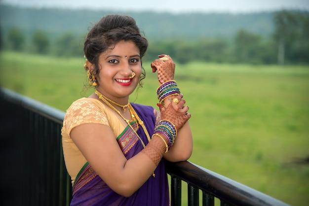 Moça indiana bonita no saree tradicional que levanta ao ar livre