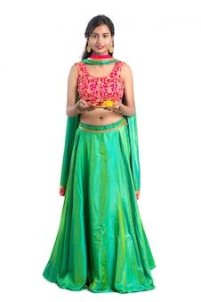 Moça indiana bonita que guarda pooja thali ou que executa a adoração em um branco