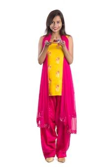 Moça indiana bonita que guarda pooja thali ou que executa a adoração em um fundo branco