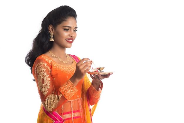 Moça indiana bonita que guarda pooja thali ou que executa a adoração em uma parede branca