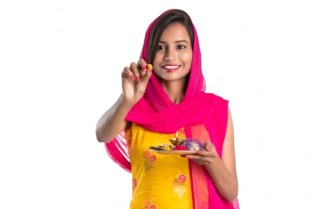 Moça indiana bonita que guarda pooja thali ou que executa a adoração