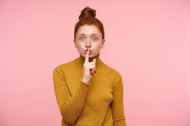 Moça, linda mulher com cabelo ruivo, sardas e coque. vestindo uma camisola de gola alta dourada e mostrando o sinal de silêncio. isolado sobre parede rosa pastel