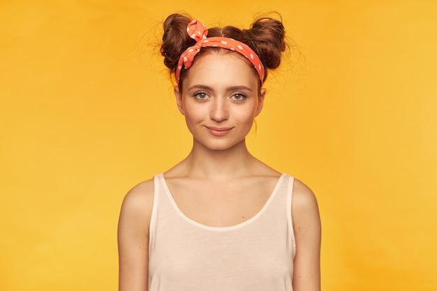 Moça, linda mulher ruiva com dois pães. vestia um top branco e uma faixa vermelha pontilhada no cabelo parecendo confiante, esperando por algo. isolado sobre a parede amarela