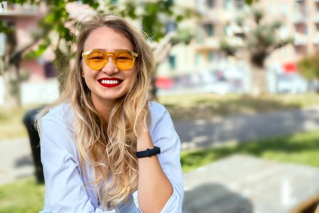 Moça loira em óculos de sol amarelos
