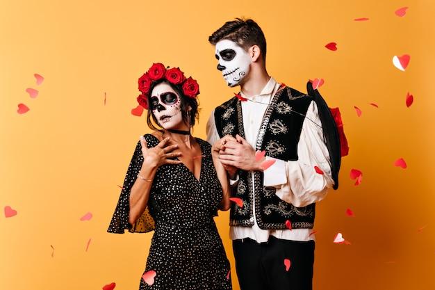 Moça mexicana impaciente em trajes tradicionais, ouvindo palavras de amor de seu jovem. retrato de casal fofo