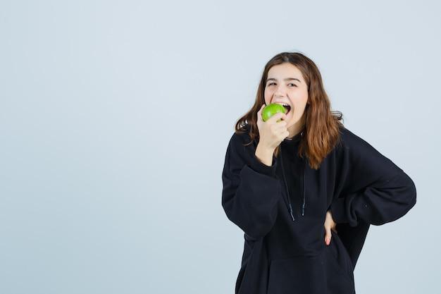 Moça mordendo maçã enquanto mantém a mão na cintura em um moletom grande, calça e parecendo encantada vista frontal.