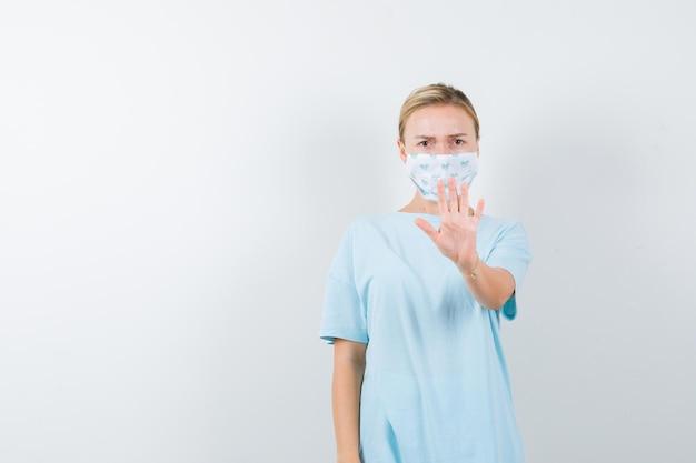 Moça mostrando gesto de parada em camiseta, máscara e parecendo séria