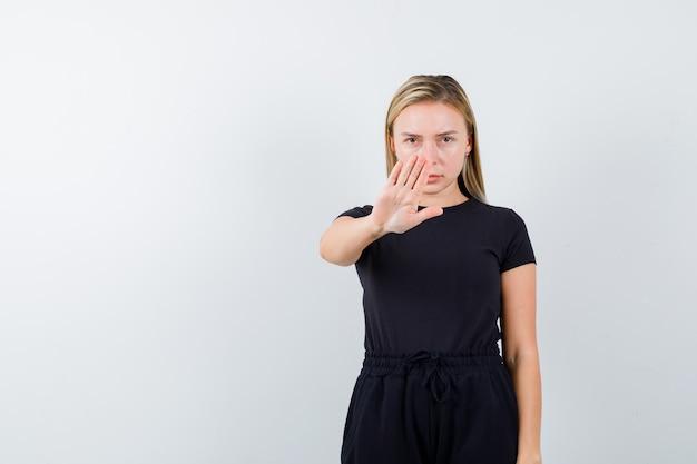 Moça mostrando gesto de parada em t-shirt, calças e olhando sério. vista frontal.