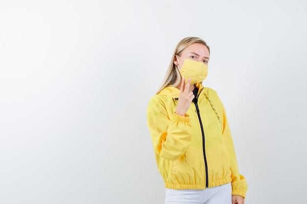 Moça mostrando o sinal de v na jaqueta, calça, máscara e parecendo confiante. vista frontal.
