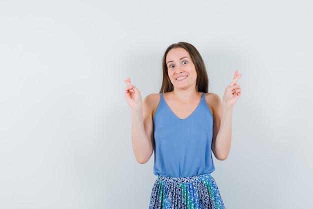 Moça mostrando os dedos cruzados na blusa, saia e olhando alegre, vista frontal.