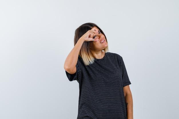 Moça mostrando sinal de tamanho pequeno em vestido pólo e parecendo alegre. vista frontal.