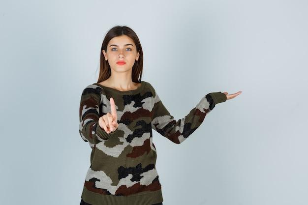 Moça mostrando um pequeno gesto enquanto finge mostrar algo no suéter