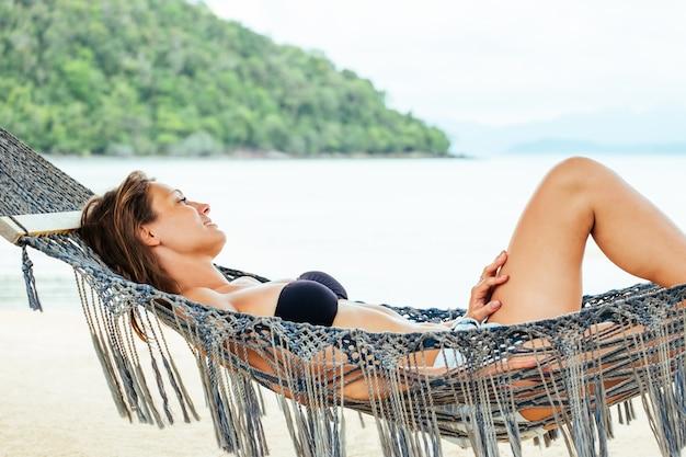 Moça muito alegre, deitado na rede na praia