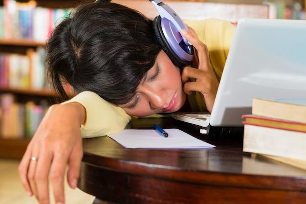 Moça na biblioteca com laptop e fones de ouvido