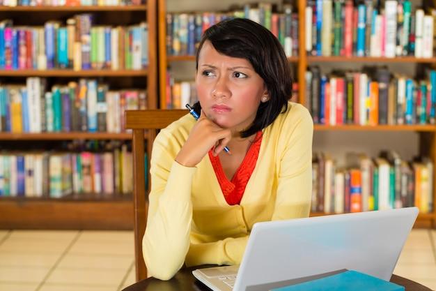 Moça na biblioteca com laptop