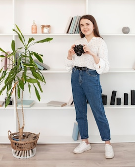 Moça na camisa branca que está com uma câmera velha