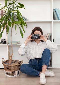 Moça na camisa branca usando uma câmera velha