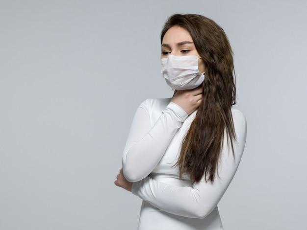 Moça na camiseta branca que prende sua garganta