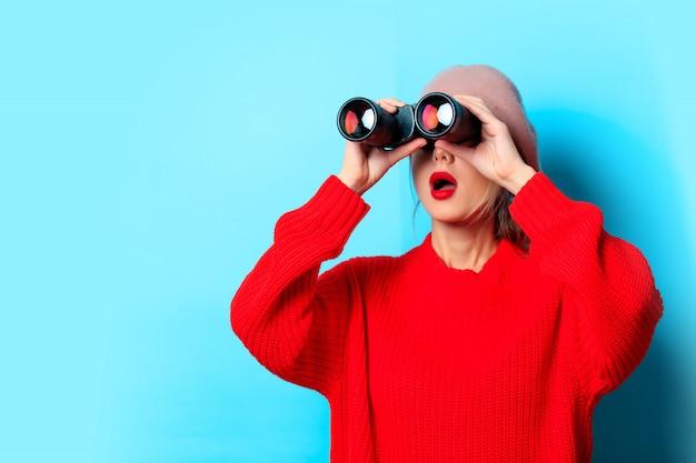 Moça na camisola vermelha com binóculo