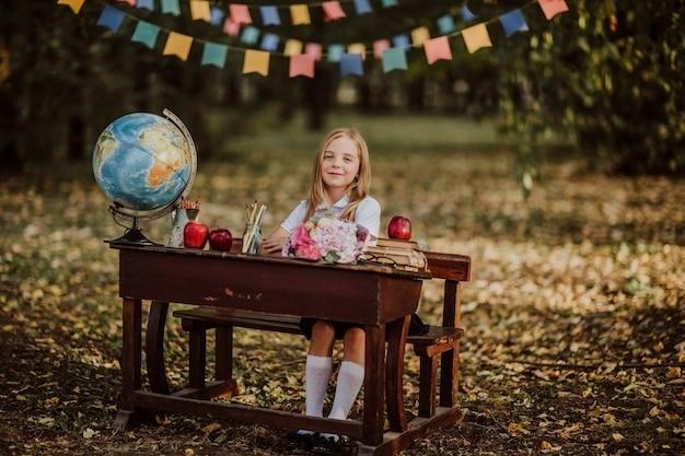 Moça na farda da escola que levanta o assento em uma mesa de madeira velha no parque