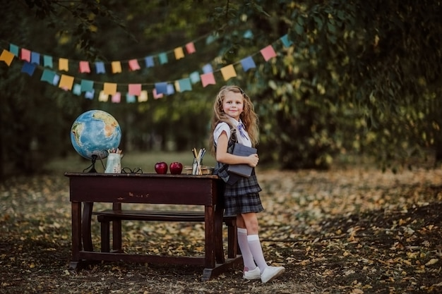 Moça na farda da escola que levanta perto de uma mesa de madeira velha no parque