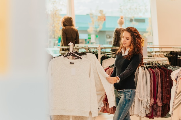 Moça na roupa de compra da loja
