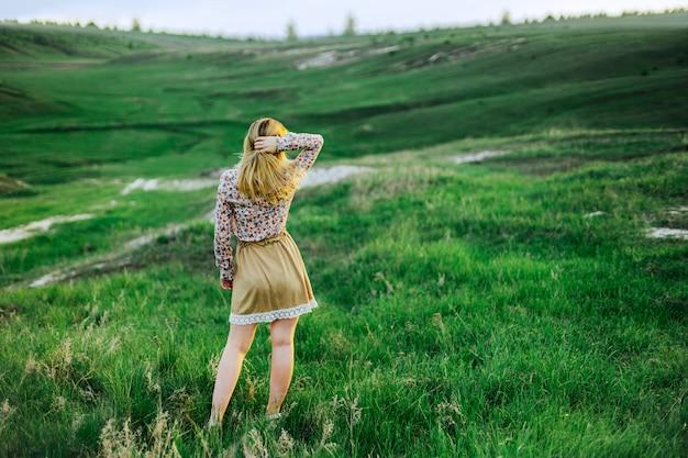 Moça nas montanhas e nos montes. olhe para a distância. inspiração. solidão, fuga