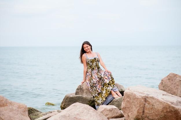 Moça nas rochas no mar