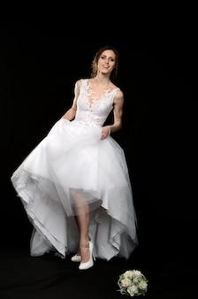 Moça no branco em um vestido de casamento com os pés descalços, noiva misteriosa feliz emocional em um fundo preto.