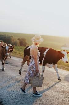 Moça no campo agrícola com vacas preto e brancas