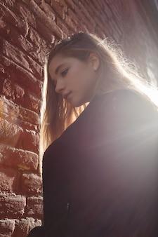 Moça no casaco preto que está na frente uma parede de tijolo na luz do sol bonita. solidão