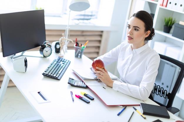Moça no escritório trabalhando com documentos e segurando uma maçã.