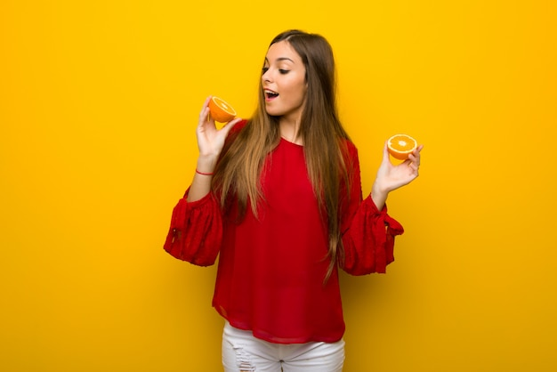 Moça no fundo amarelo vibrante com laranjas
