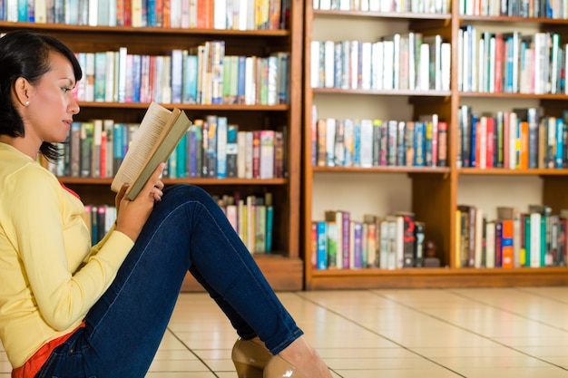 Moça no livro de leitura da biblioteca