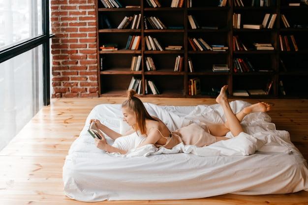 Moça no livro de leitura do negligee na cama