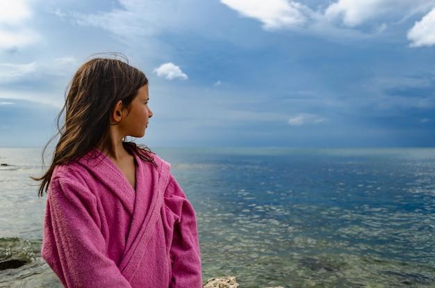 Moça no roupão de banho na praia, clima de tempestade no espaço.