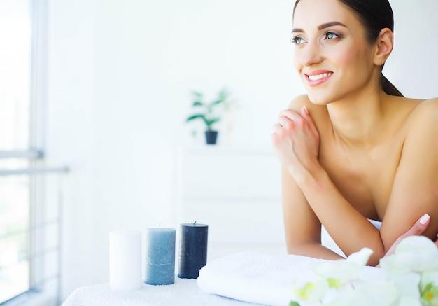 Moça no salão de beleza, mulher moreno com olhos verdes, encontrando-se nas tabelas da massagem, pele limpa e fresca, cuidado de pele,