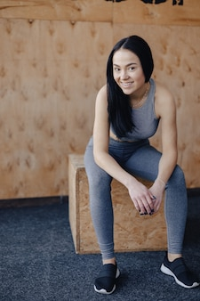 Moça no sportswear em um gym em um fundo simples, um tema da aptidão, e esporte