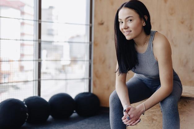 Moça no sportswear em um gym em um fundo simples, um tema da aptidão, um crossfit e esporte