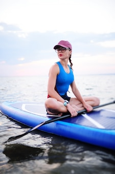 Moça no sportswear que senta-se em uma placa do sup
