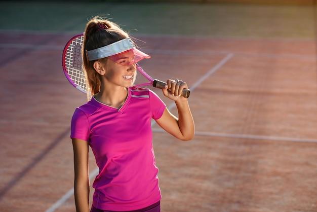 Moça no tampão à moda e sportswear com raquete no ombro no fundo da luz do sol. jogadora de tênis na quadra ao ar livre no ocaso.