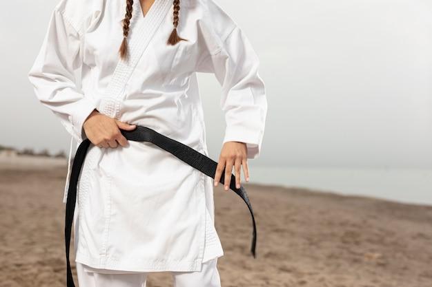 Moça no traje das artes marciais